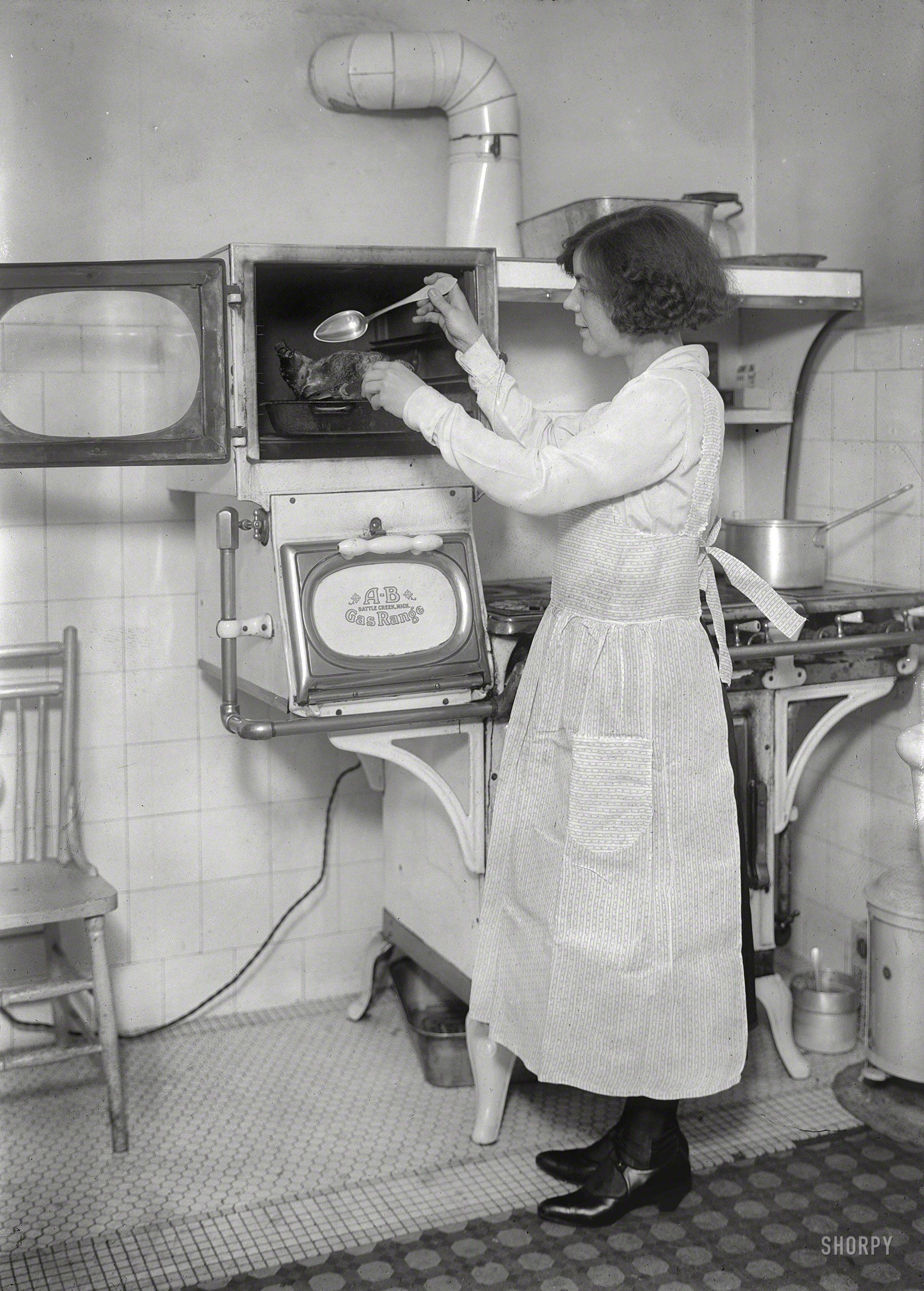 British pianist and conductor Ethel Leginska bastes her bird in a double gas oven. Circa 1921 in New York
