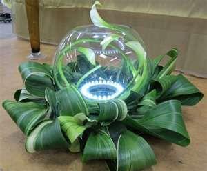 Hojas verdes con cilindro o ánfora de cristan con relleno de pocas flores y vela flotante.