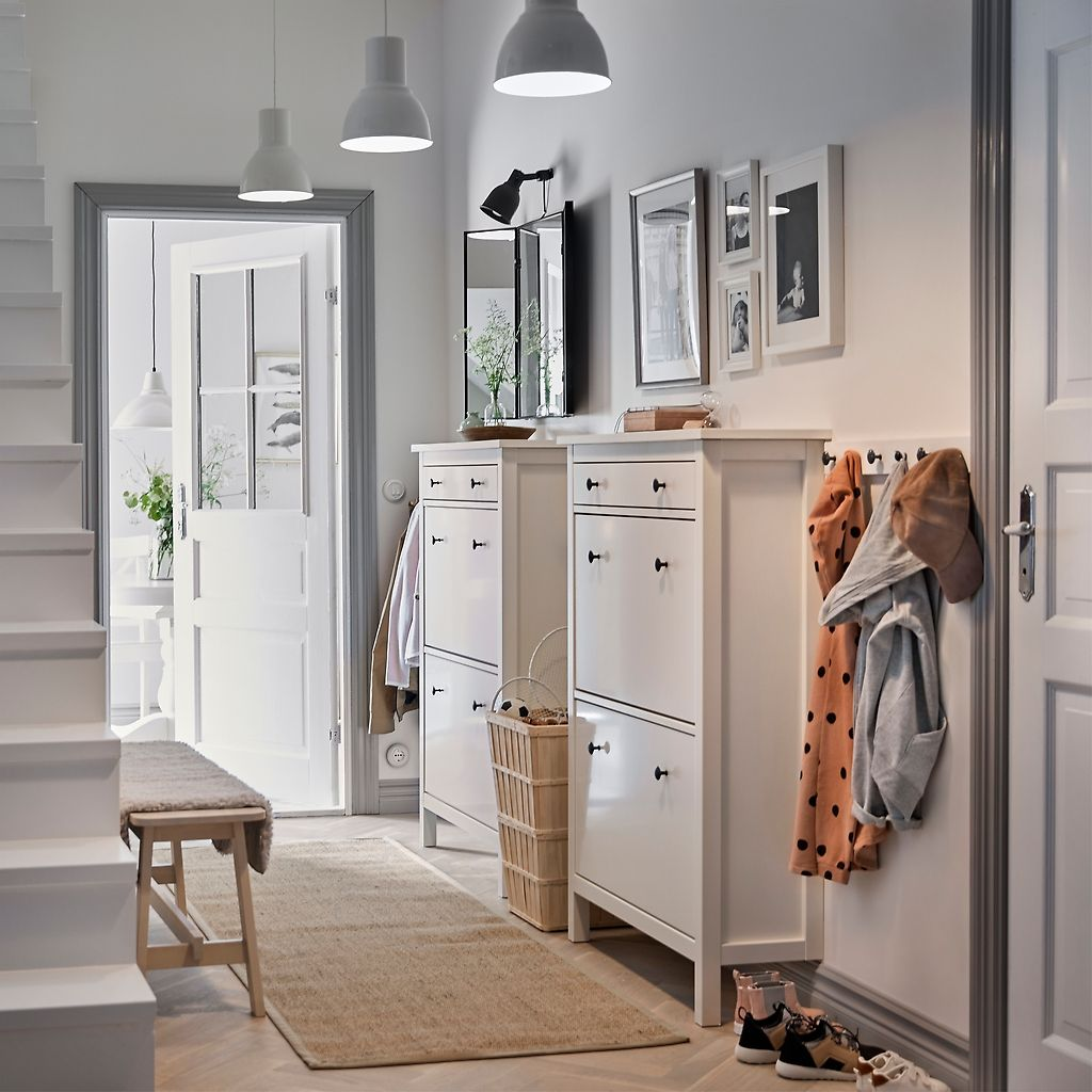 Hallway storage for coats  A white hallway with two traditional white HEMNES shoe cabinets side