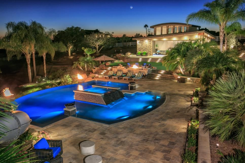 Backyard Oasis Designs tropical pool oasis with water features and fire pit | fire pit