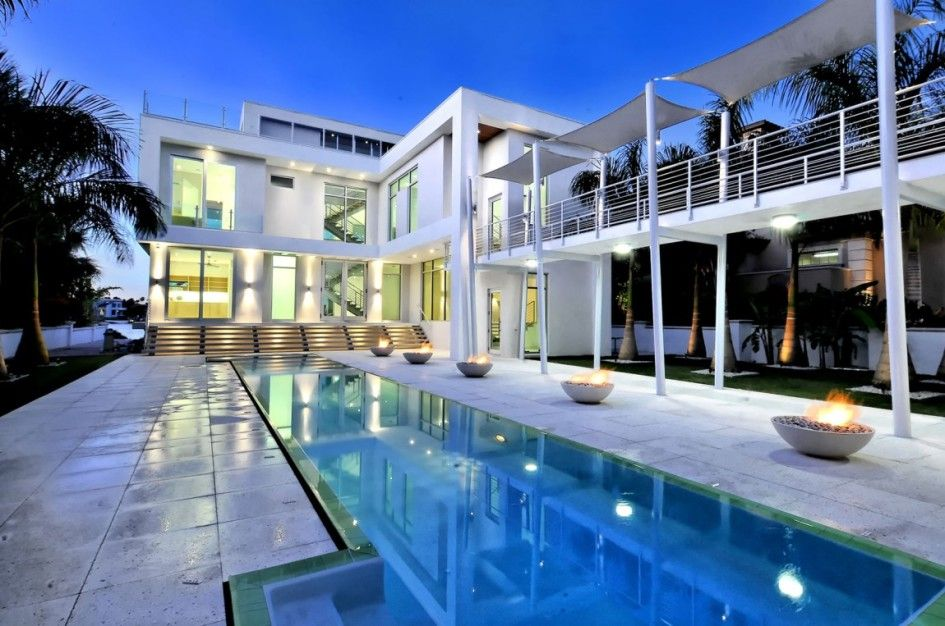 Architecture, Amazing Home Courtyard With Swimming Pool And Beautiful Lush Palm Trees Featuring White Bridge With Membrane Cover: Waterfront Home Design with Bright White Interior and Fresh Atmosphere