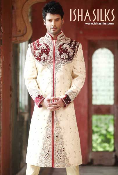 The Cream Banarasi Sherwani with maroon brocade stone work along with chudi pant is the one to make the occasion memorable.   The onlookers gasp with awe and admiration, and bless the couple with the best wishes for the journey ahead. A great pick among Indian wedding dresses.