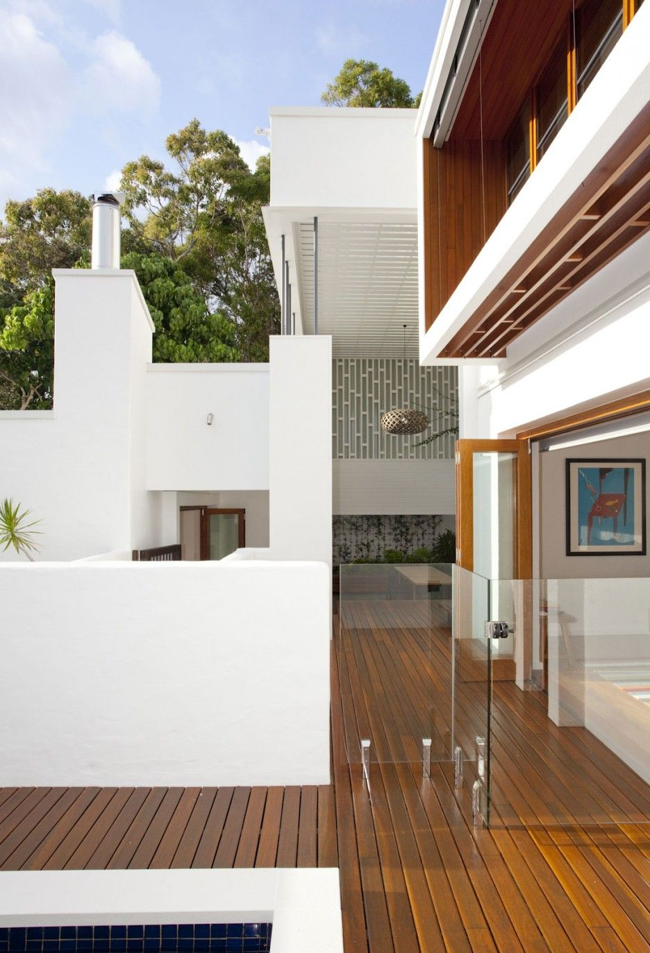 Contemporary sunshine beach house exterior with wooden floor white and glass fencing and cozy sitting with pendant lamp