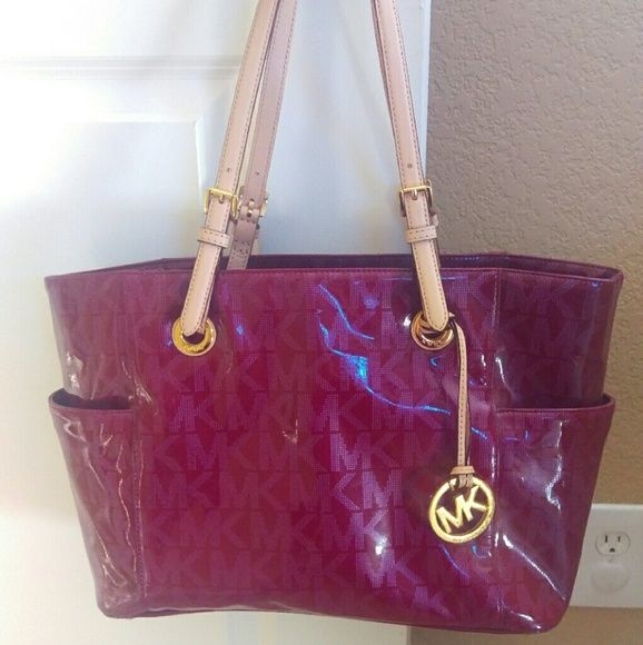 "Michael Michael Kors Signature Maroon Tote MICHAEL Michael Kors Signature Patent East West Purse Tote Nickel Metalic Shoulder. Supple patent leather is outfitted with shiny golden hardware and iconic MK monogram pattern, while the pocket-lined interior easily meets all your daily demands. Imported MICHAEL Michael Kors bag patent leather; trim: Vachetta leather Double handles with 9"" drop Silver-tone hardware; 2 side slip pockets; has a few small blemishes on inside of tote. MICHAEL Michael…"