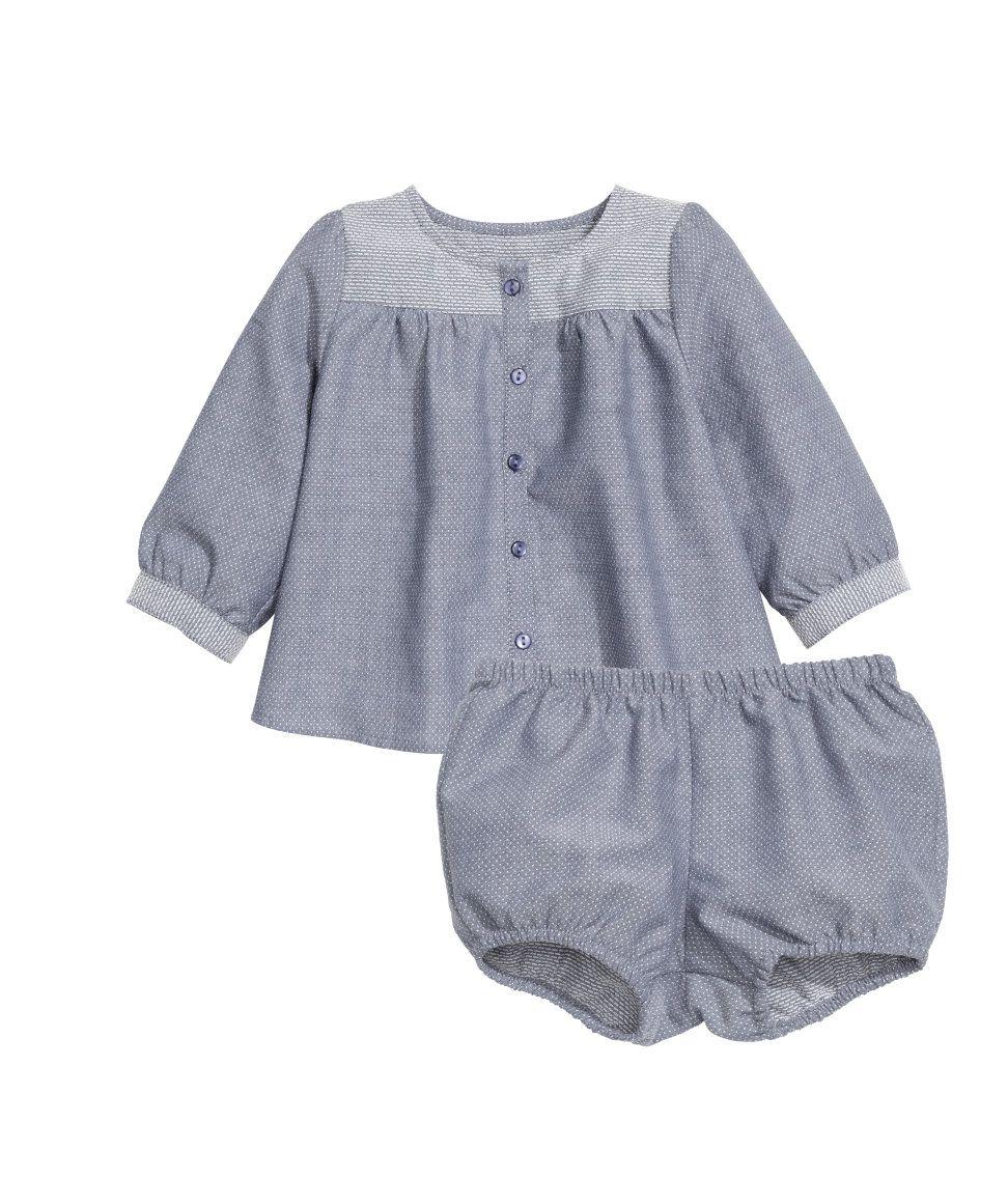 BABY EXCLUSIVE/CONSCIOUS. Een set van dobbygeweven biologisch katoen bestaande uit een blouse met lange mouwen en een pofbroekje. De blouse heeft een knoopsluiting voor en een schouderpas in een contrasterende kleur. Het pofbroekje heeft elastiek in de taille en rond de beenopeningen.