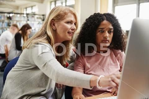 And Female Student Work On Computer In College Library Stock Photos StudentWorkTeacherFemaleTeacher And Female Student Work On Computer In College Library Stock Photos St...