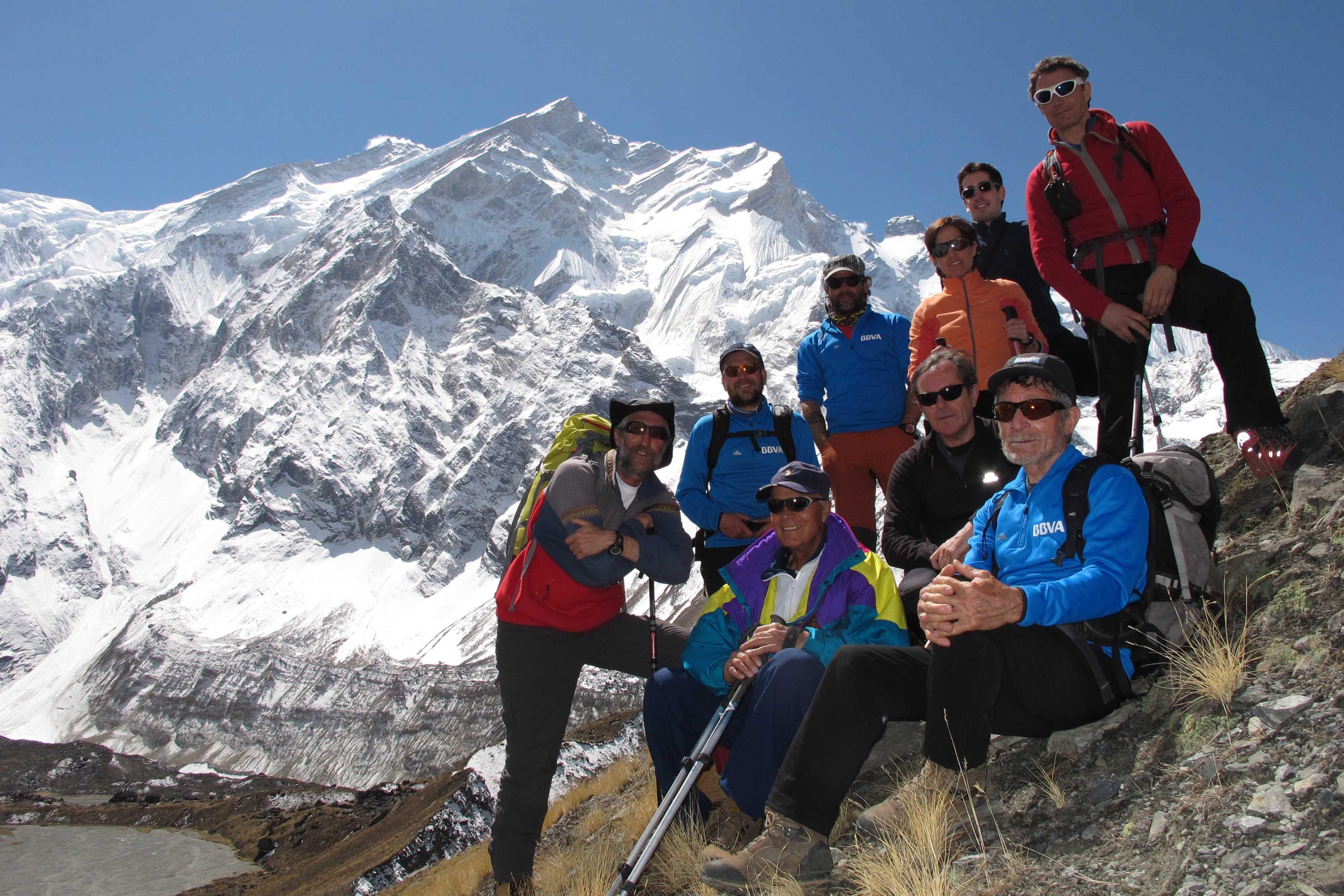 Carlos Soria, con la cara oeste del Annapurna al fondo, posa junto con sus compañeros de expedición y un grupo de clientes de BBVA cuya visita ha recibido hoy en el campo base.