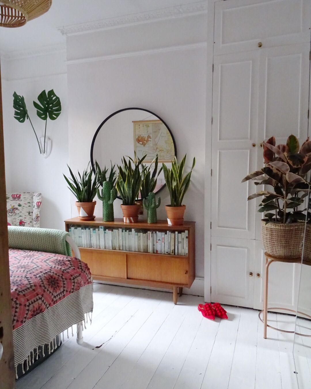 vintage bedroom ideas with plants Boho bedroom - white floors, round mirror, vintage sideboard and mother in law's tongue plants