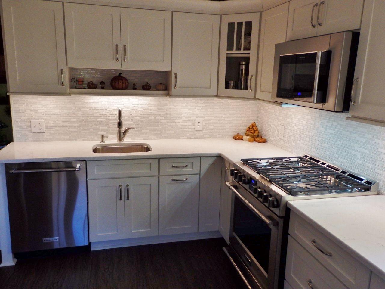 Pental quartz misterio engineered quartz countertops with a white glass and stone mosaic tile backsplash white kitchen by stoneshop from cherry hill nj