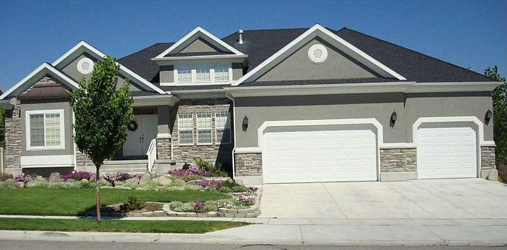 Gray stucco with rock accent and white trim goes well for Stucco house paint colors