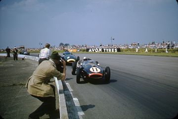Jack Brabham in his Cooper leads the Vanwall of Tony Brooks as photographers lean out over the track. Silverstone, 1958.
