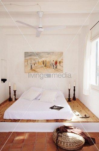 Mediterranes Schlafzimmer mit Matratze auf Podest und ...