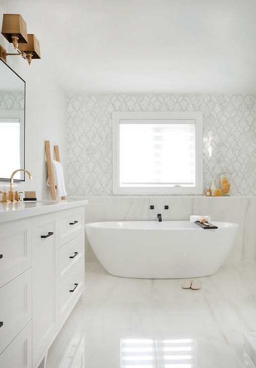 Freestanding Oval Tub Under A Window Framed By White And