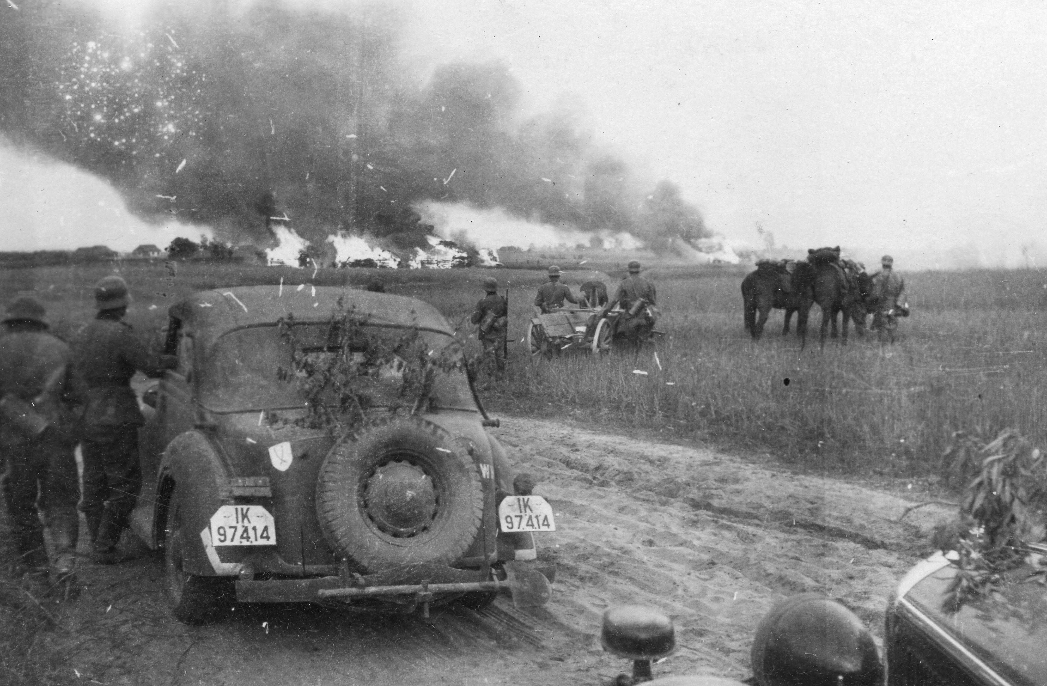 German soldiers watch a Soviet village burn