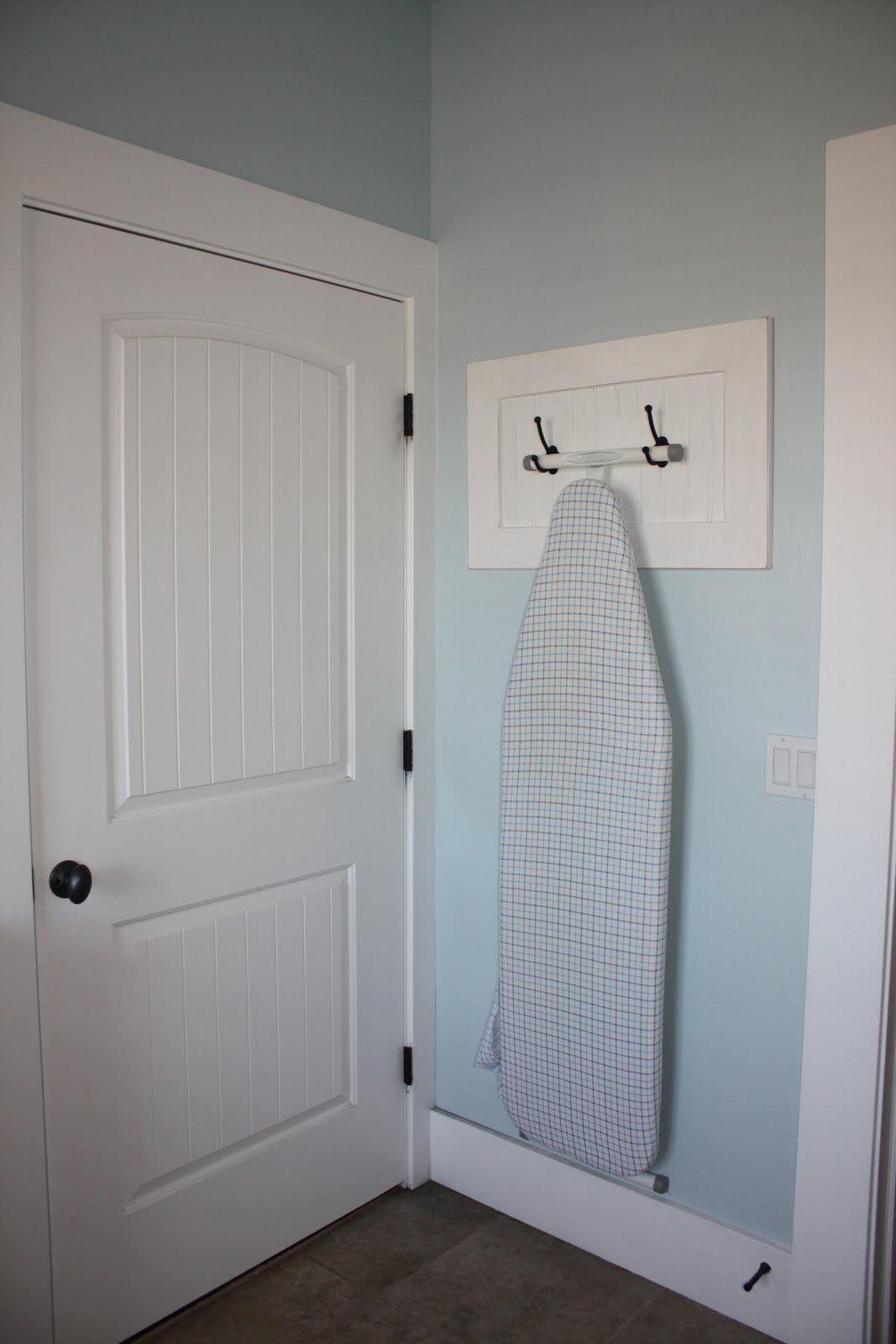 2 robe hooks make easy way to hang an ironing board - I'm going to make this!!!