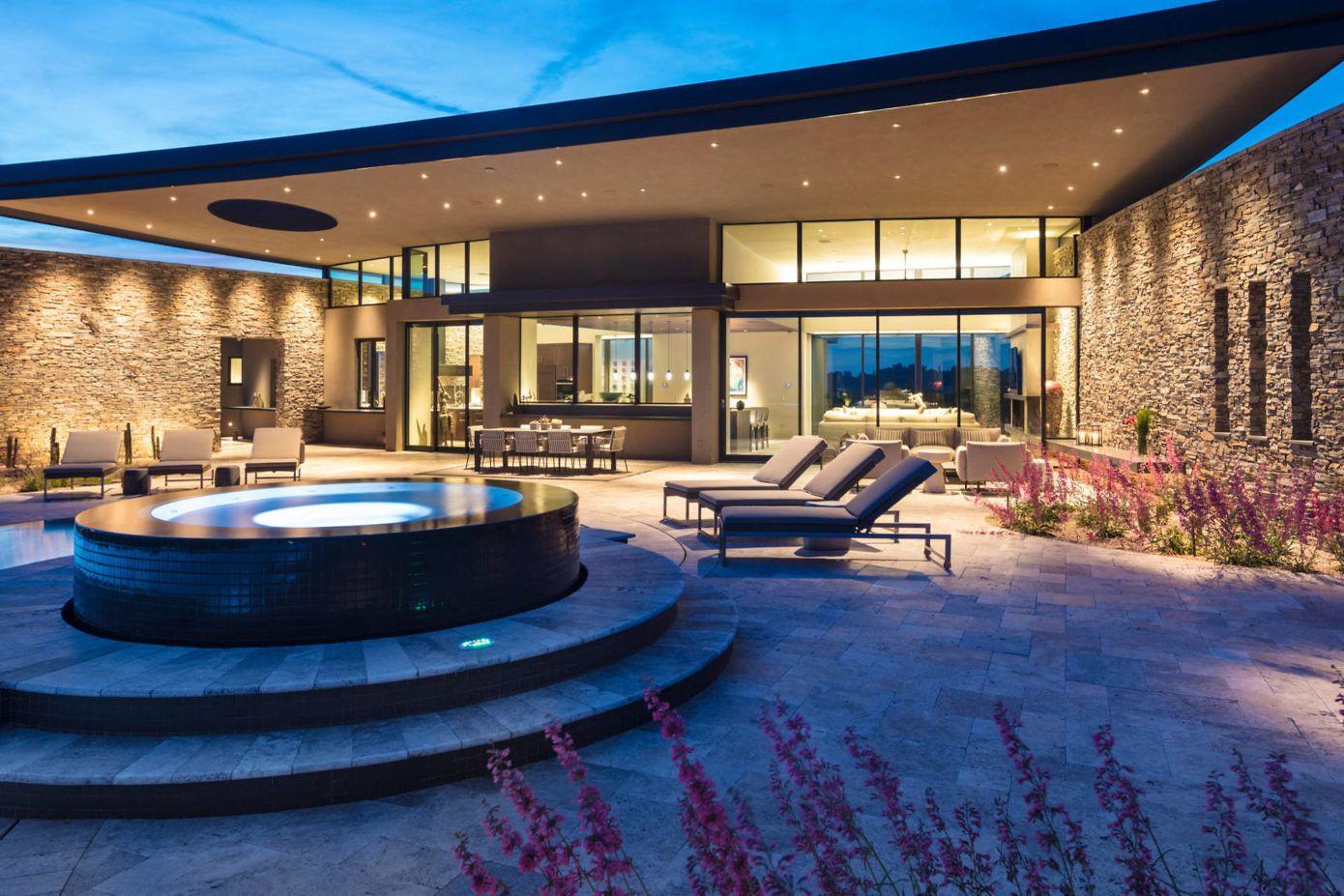 Modern desert home set on a rocky hillside with ...
