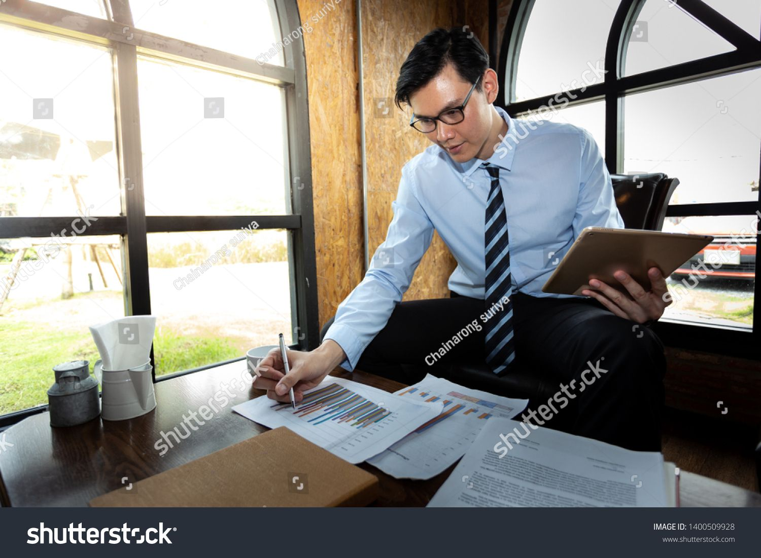 A Businessman Is Writing On Paper While Working On Tablet In