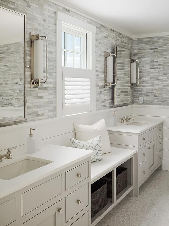 Photo of White and gray bathroom boasts top half of walls clad in gray marble mosaic tile…