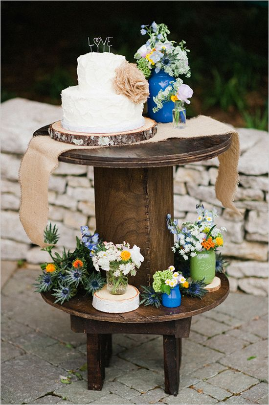 "A rustic wedding cake display. The table has various flower arrangements and burlap elements. The cake is on a wooden slab and has a topper with the word ""love""."