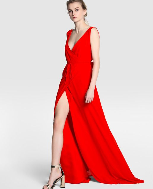 Vestido largo en color rojo. Sin mangas, con escote cruzado y adorno de rosas en la cintura.