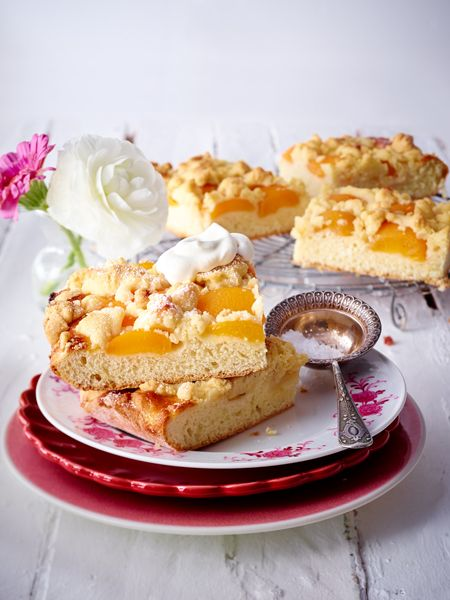 Aprikosenkuchen mit Macadamiastreuseln  Zutaten (24 Stücke)  750 g Mehl, 130 g Zucker, 2 Päckchen Vanillin-Zucker, Salz, 220 g weiche Butter, 1 Ei, 250 ml Milch, 1 Würfel frische Hefe, 150 g Macadamianusskerne, 2 Dosen Aprikosen, 4 EL Aprikosen-Konfitüre, Fett und Mehl für die Fettpfanne, Mehl für die Arbeitsfläche