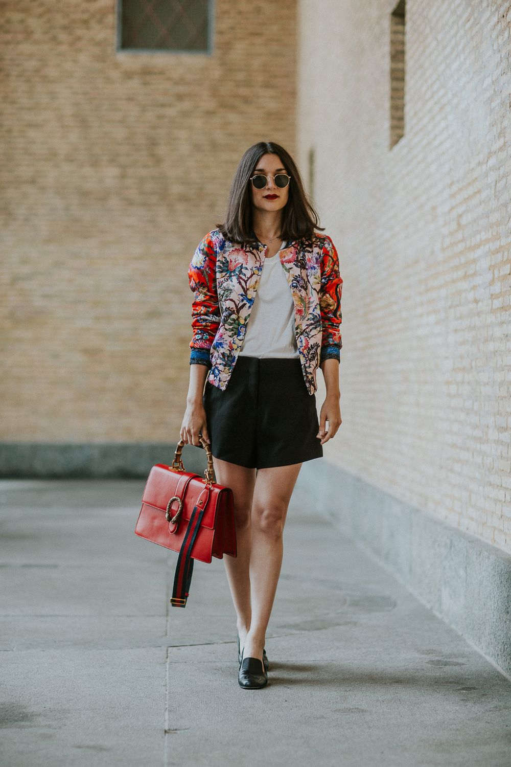 Anisa Sojka styles colorful floral rainbow H&M bomber with oriental details and glitter cuffs   Simple white t-shirt   Black a-line shorts   Gucci loafers with signature GG logo   Red Dionysus Gucci handbag with gold snake and bamboo / striped over the shoulder handle   Classic round Rayban sunglasses   Red lipstick   Straight shoulder length brunette hair   Fashion blogger street style shot in London by Mikael Miettinen & Mikaela Watsfeldt