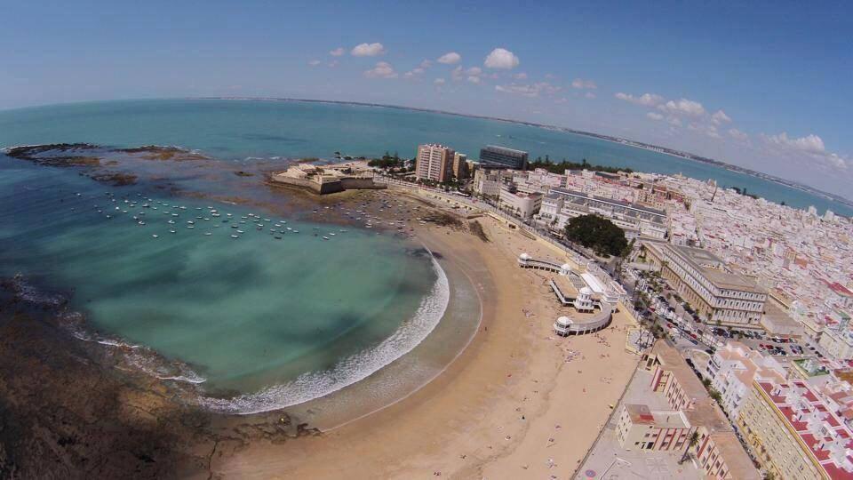 Playa de la Caleta desde el cielo, sus rocas, uno de sus castillos, su balneario, preciosa imagen de una playera super acogedora.