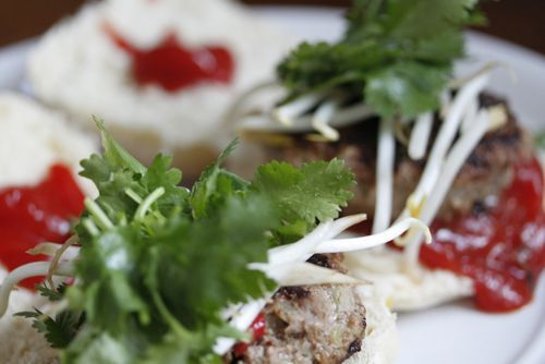 Divine beef burgers topped with bean sprouts and coriander