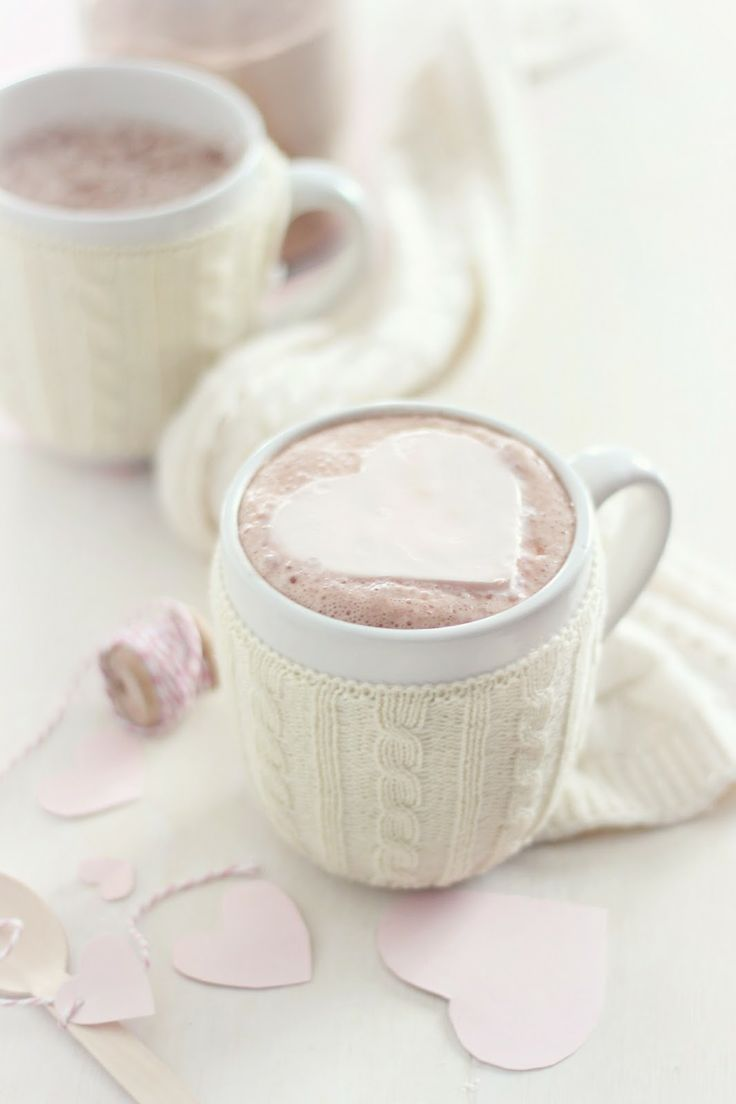 Hot chocolate with heart shaped marshmallow, and sweater cup cozy.