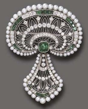 A BELLE ÉPOQUE EMERALD, DIAMOND AND SEED PEARL PENDANT BROOCH, BY J.E. CALDWELL & CO. The pierced old European-cut diamond plaque, enhanced by alternating old European-cut diamond and calibré-cut emerald detail, to the seed pearl trim and central sugarloaf cabochon emerald, suspending a pendant of similar design, mounted in platinum, circa 1915, signed J.E.C & Co., numbered.