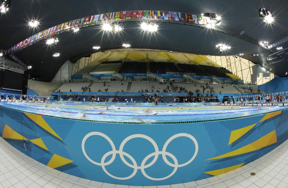 in this photo taken with a fisheye lens swimmers practice in the pool at the - Olympic Swimming Pool 2012