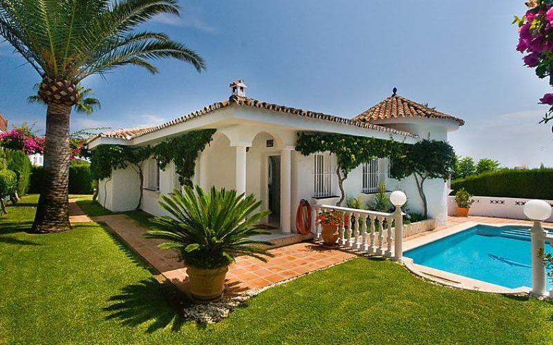 Verdure, palmiers, soleil et belle piscine autour de cette maison de