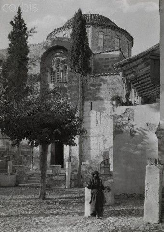 A person stands outside of the Convent of Daphne on the Sacred Way-Fred Boissonnas