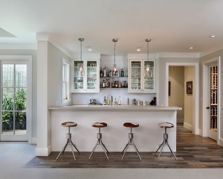 Wet Bar With A Trio Of Clear Glass Pendants Illuminating Paneled