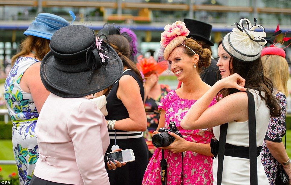 Enjoying themselves: Ladies stop to chat as they enjoy their day out at Ascot, with one lady looking particularly elegant in a pink lace dre...