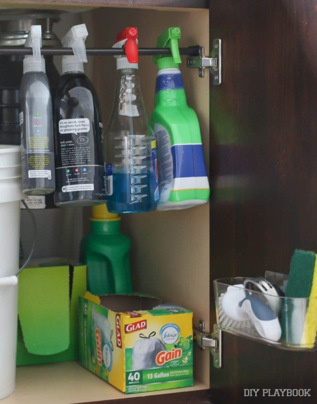 Easy ways to get organized under the kitchen sink. Love this easy DIY project for a little extra organization in the kitchen. Make the most of your space and add a tension rod for spray bottles, a cabinet mount for sponges, and even a drawer for extra cleaning supplies!