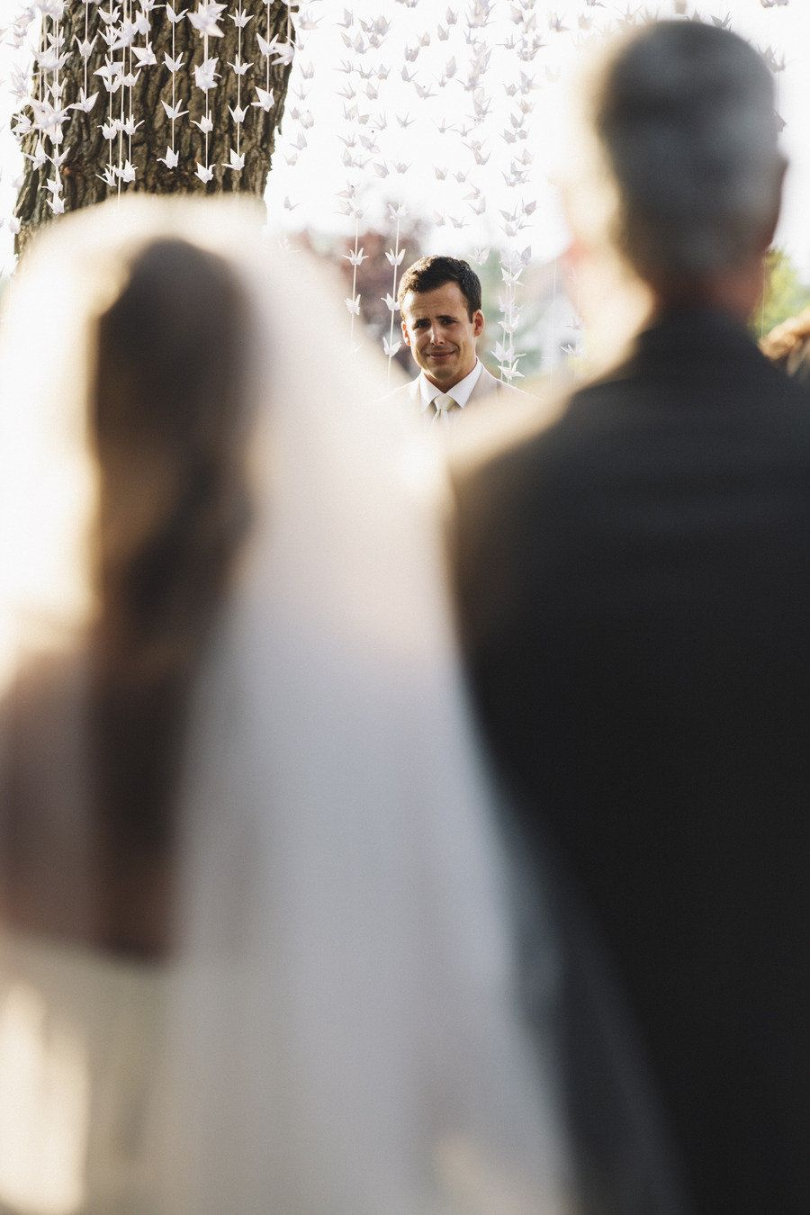 Picture of the groom from behind the bride as she walks down the aisle with her father