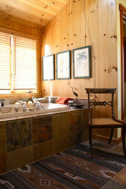 Wood paneling & slate bathtub make master bath feel straight out of a cabin deep in the forest