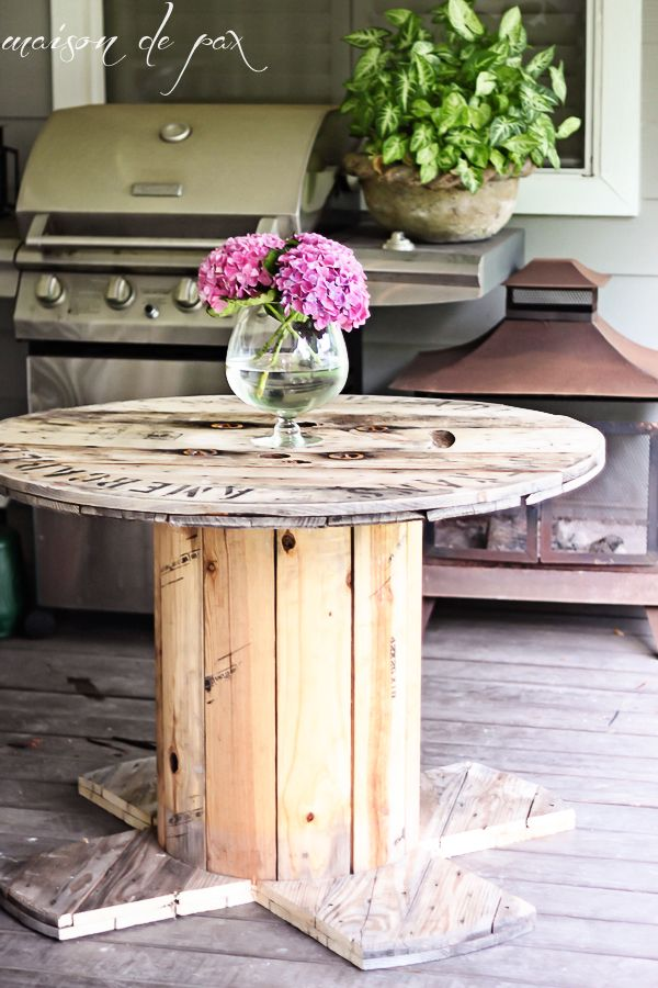 Mesa usando carretel de madeira com  os pés quadrados.