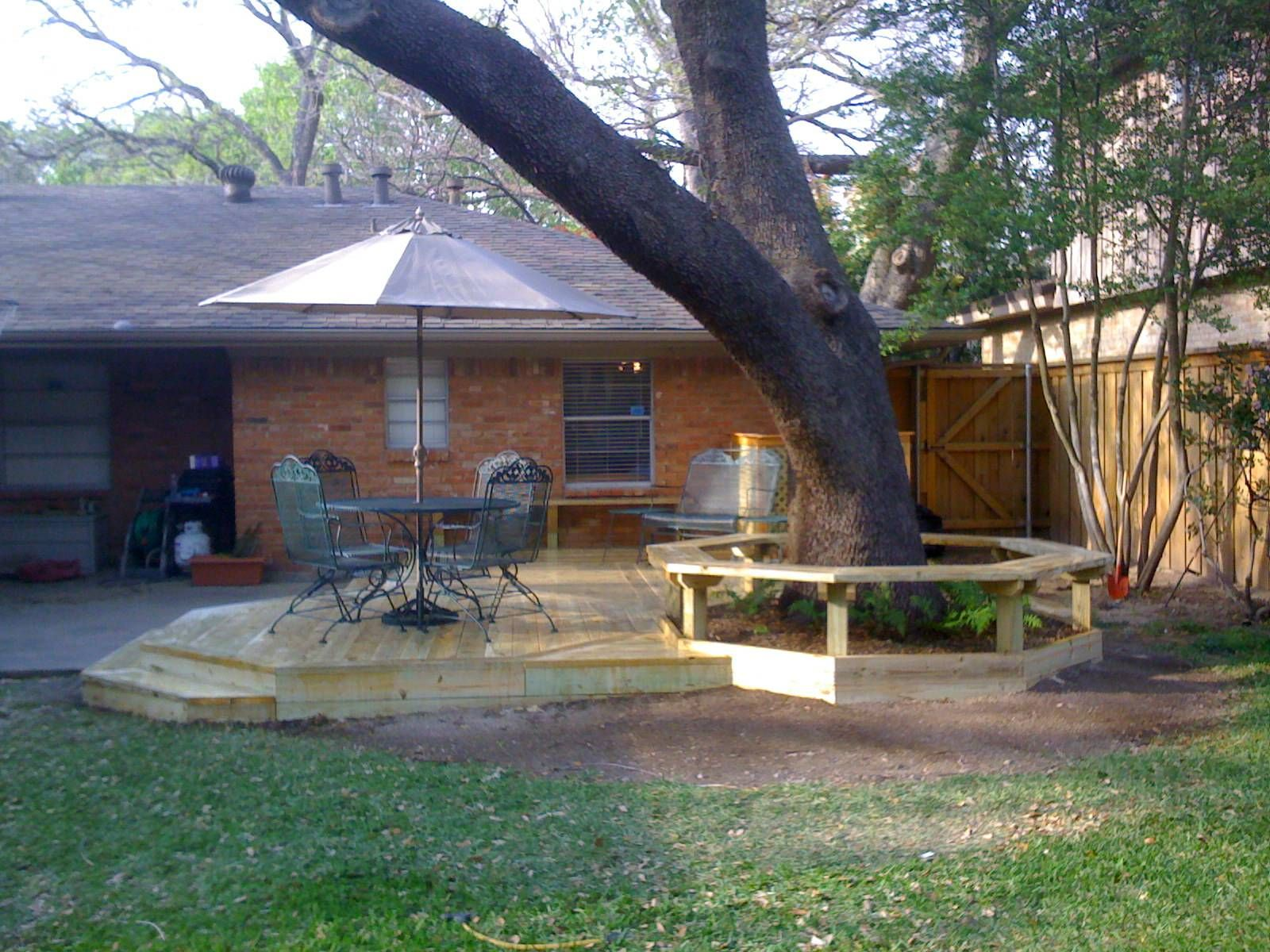 Small backyard deck under the big tree with round table for Small backyard decks