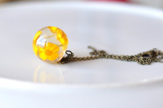 This is a beautiful truncated ball with crystal clear resin and yellow wildflowers. It is a mystical piece of jewelry that can be worn with casual