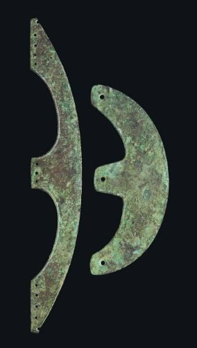 TWO EGYPTIAN BRONZE OR COPPER ALLOY AXE BLADES  MIDDLE KINGDOM, 12TH DYNASTY, CIRCA 1985-1773 B.C.  Comprising one of elongated crescentic form with three attachment tangs, each pierced for bindings; and one of crescentic form with three attachment tangs, each with single piercing  12 5/8 in. (32 cm.) long and 7 ½ in. (19 cm.) long respectively