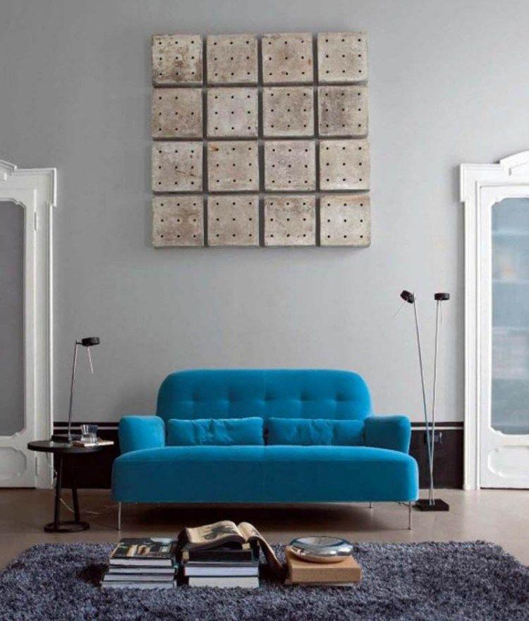 blaue couch in türkis im mittelpunkt und wanddeko aus platten ...