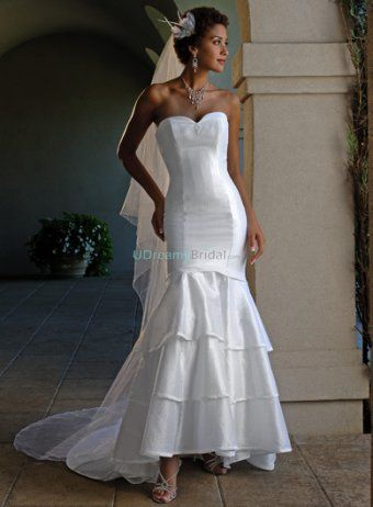 This mermaid gown is an excellent example of top bridal fashion trends. Fitted sweetheart bodice shows hourglass curve perfectly. Tiered skirt adorned with a bow tie accenting in the back hits at ankles. Sweep train. Colors available in Color Options. Custom-to-measurement for any sizes.