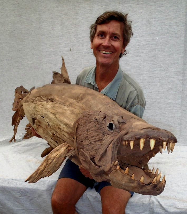 A goliath tigerfish driftwood sculpture by tony