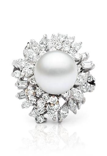 Curated by Colin Cowie, this decadent vintage ring features a 12mm white cultured pearl surrounded by 48 diamonds of various cuts totaling 2.88 carats.