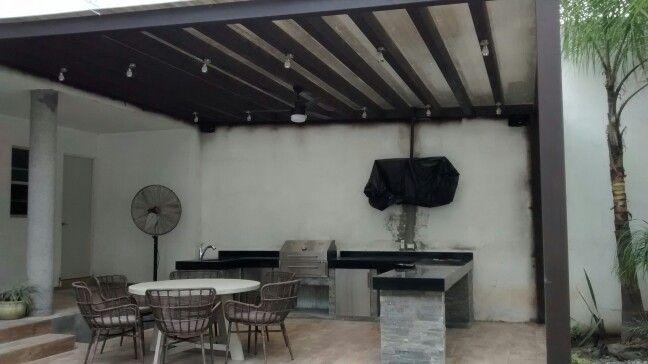 Un patio donde se contruyo una pergola en acero com techo for Asador en patio pequeno