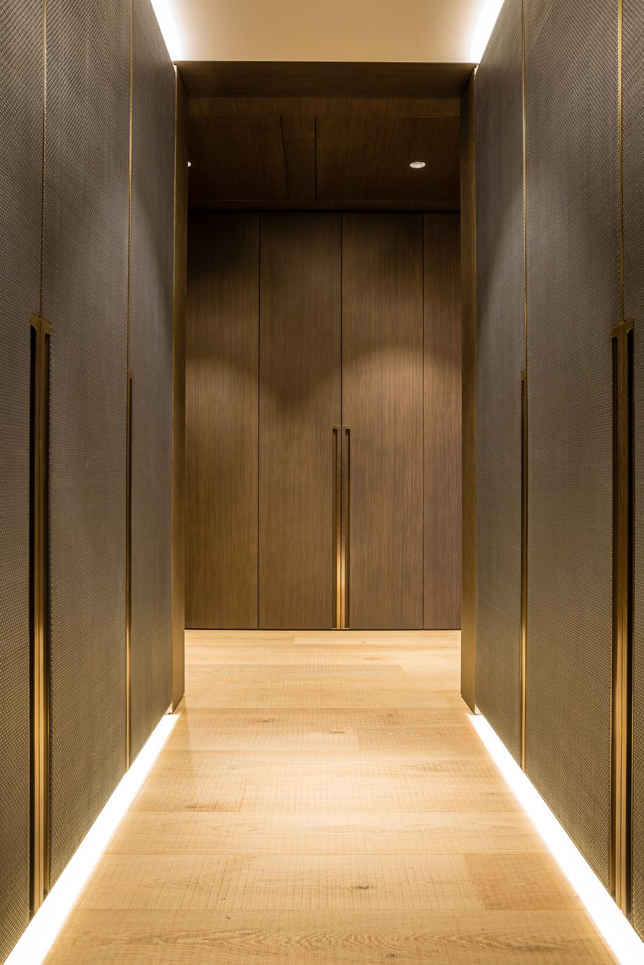 Case study - One Hyde Park, Knightsbridge. Design - Grangewood Finchatton. Joinery - INTERIOR-iD. Dressing Room with antique brass metal detailing, bespoke recessed handles fully integrated into framed wardrobe doors with woven leather and dark stained Zebrano timber.