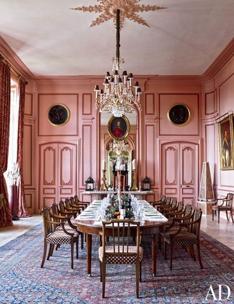 FORMAL DINING ROOM Above the mantel in the rose-pink formal dining room hangs a portrait by Nicolas de Largillière, and at far right is an image of Napoléon III. The table and chairs are 19th-century English, and the carpet is from Doris Leslie Blau.