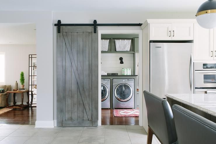 A Gray Barn Door On Rails Opens To A Cottage Laundry Room
